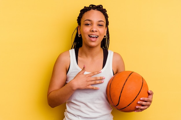 Junge afroamerikanerfrau, die basketball spielt, der auf gelbem hintergrund lokalisiert wird, lacht laut und hält hand auf brust.