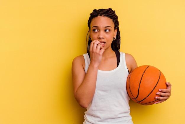 Junge afroamerikanerfrau, die basketball spielt, der auf gelber wand lokalisiert entspanntes denken über etwas betrachtet, das einen kopienraum betrachtet.