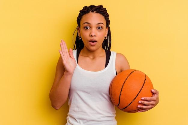 Junge afroamerikanerfrau, die basketball spielt, lokalisiert auf gelbem hintergrund überrascht und schockiert.
