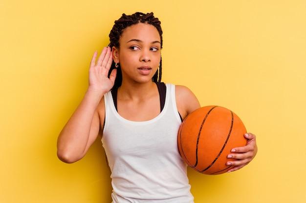 Junge afroamerikanerfrau, die basketball spielt, lokalisiert auf gelber wand, die versucht, einen klatsch zu hören.