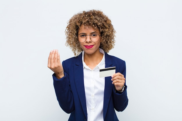Junge afroamerikanerfrau, die capice-geste macht und eine kreditkarte hält