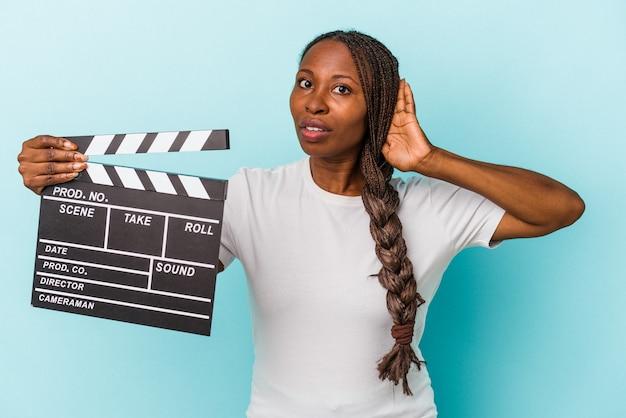 Junge afroamerikanerfrau, die clapperboard lokalisiert auf blauem hintergrund hält und versucht, einen klatsch zu hören.