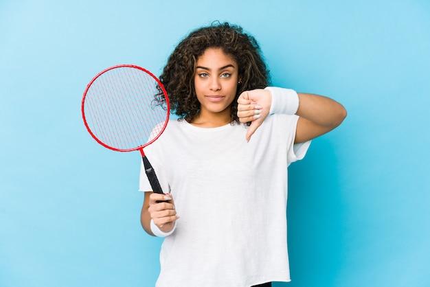 Junge afroamerikanerfrau, die das badminton zeigt eine abneigungsgeste, daumen unten spielt. uneinigkeit konzept.