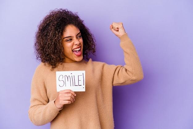 Junge afroamerikanerfrau, die ein lächelnfahne hält
