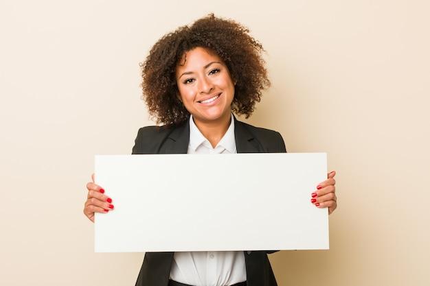 Junge afroamerikanerfrau, die ein plakat glücklich, lächelnd und nett hält.