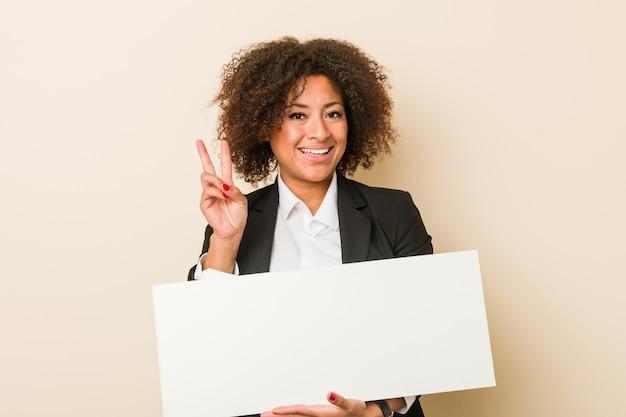 Junge afroamerikanerfrau, die ein plakat hält, das nummer zwei mit den fingern zeigt.