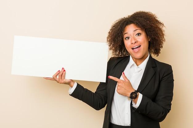 Junge afroamerikanerfrau, die ein plakat lächelt hält, freundlich zeigend mit dem zeigefinger weg.