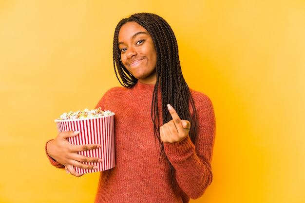 Junge afroamerikanerfrau, die ein popcorn isoliert hält, zeigt mit dem finger auf sie, als ob die einladung näher kommt.