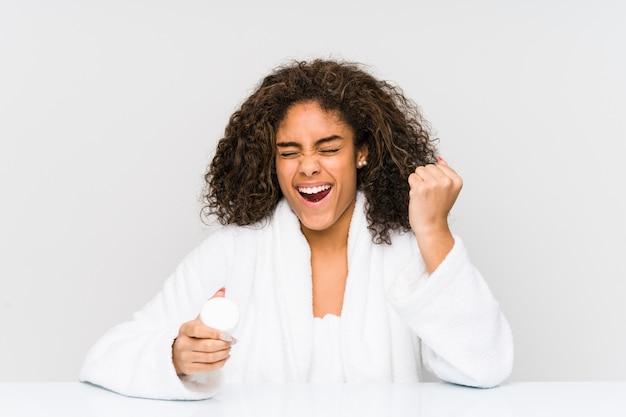 Junge afroamerikanerfrau, die eine feuchtigkeitscreme hält, die sorglos und aufgeregt jubelt. siegeskonzept.