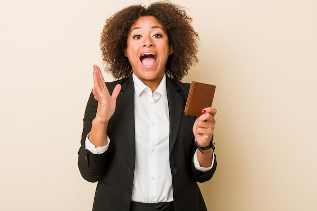 Junge afroamerikanerfrau, die eine geldbörse feiert einen sieg oder einen erfolg hält