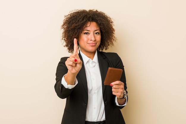 Junge afroamerikanerfrau, die eine geldbörse zeigt nummer eins mit dem finger hält.