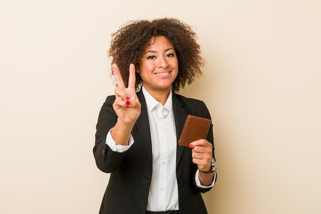 Junge afroamerikanerfrau, die eine geldbörse zeigt nummer zwei mit den fingern hält.