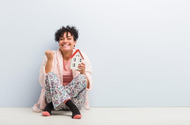 Junge afroamerikanerfrau, die eine hausikone halten sitzt