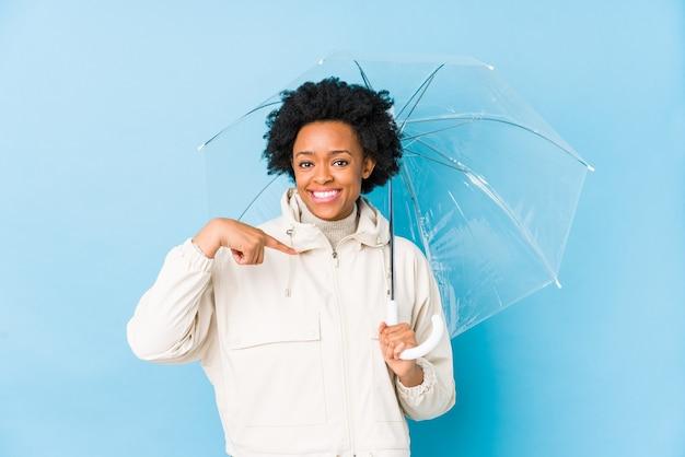 Junge afroamerikanerfrau, die eine isolierte person des regenschirms hält, die von hand auf einen hemdkopierraum zeigt, stolz und zuversichtlich