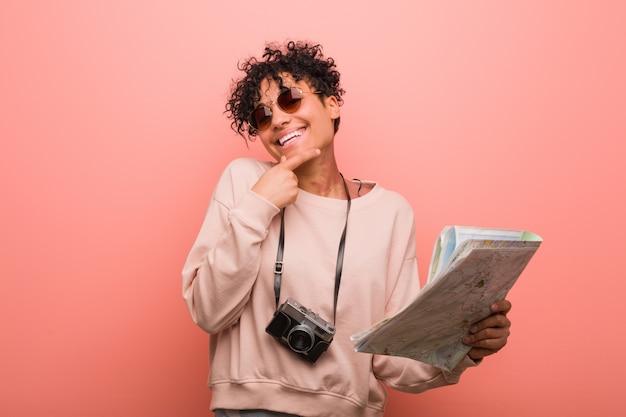 Junge afroamerikanerfrau, die eine karte seitlich schaut mit zweifelhaftem und skeptischem ausdruck hält.