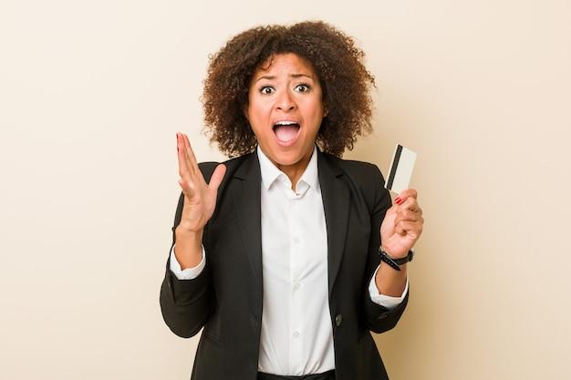 Junge afroamerikanerfrau, die eine kreditkarte feiert einen sieg oder einen erfolg hält