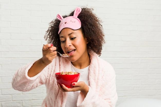 Junge afroamerikanerfrau, die eine müslischüssel auf dem bett isst
