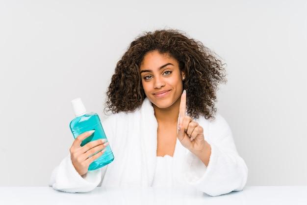 Junge afroamerikanerfrau, die eine mundwäsche zeigt nummer eins mit dem finger hält.