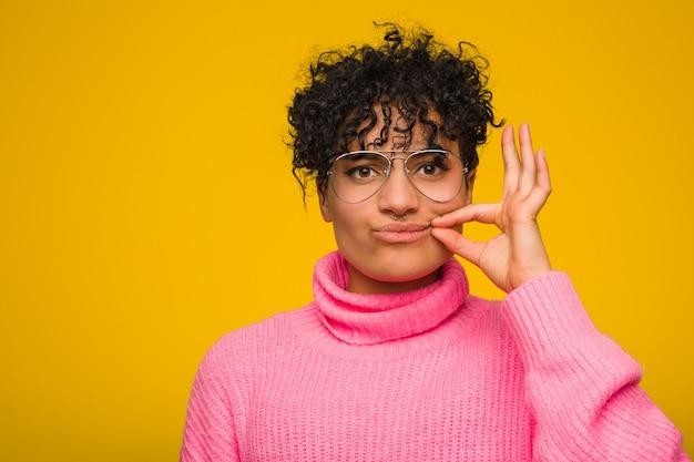 Junge afroamerikanerfrau, die eine rosa strickjacke mit den fingern auf den lippen halten ein geheimnis trägt.