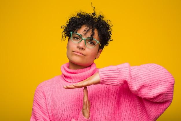 Junge afroamerikanerfrau, die eine rosa strickjacke zeigt eine auszeitgeste trägt