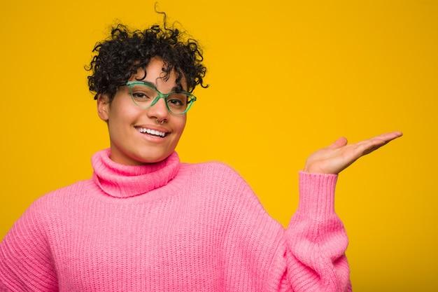 Junge afroamerikanerfrau, die eine rosa strickjacke zeigt einen kopienraum auf einer palme trägt