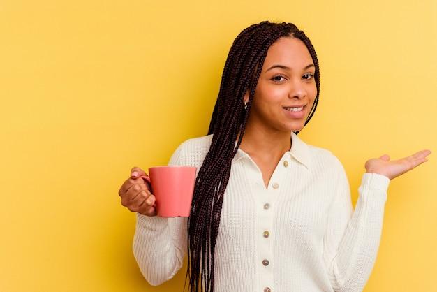 Junge afroamerikanerfrau, die eine tasse lokalisiert hält, die einen kopienraum auf einer handfläche zeigt und eine andere hand auf taille hält.
