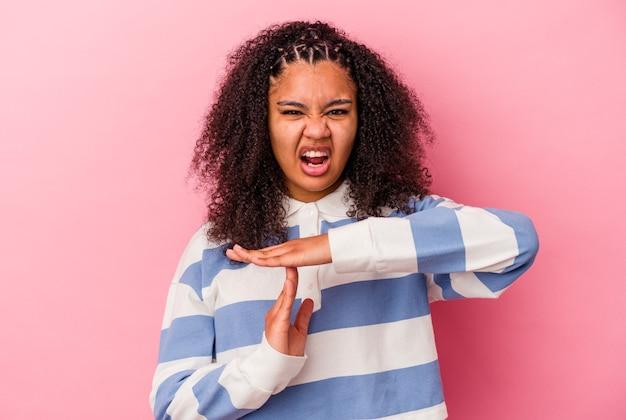 Junge afroamerikanerfrau, die eine zeitüberschreitungsgeste zeigt.