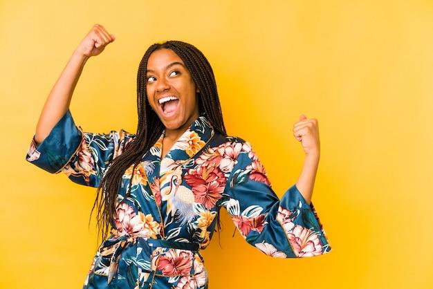 Junge afroamerikanerfrau, die einen asiatischen pijama trägt, der faust nach einem sieg erhebt