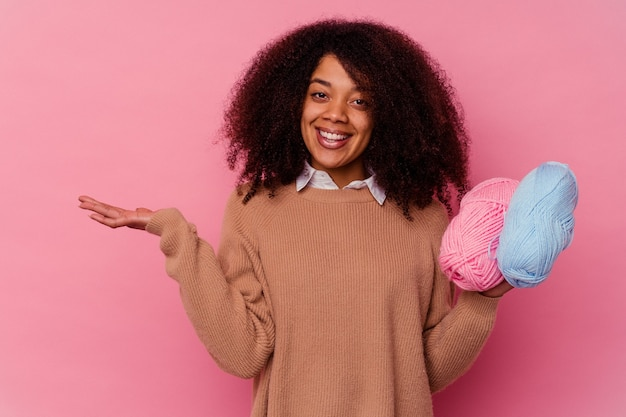 Junge afroamerikanerfrau, die einen auf rosa isolierten nähfaden hält, der einen kopienraum auf einer handfläche zeigt und eine andere hand auf taille hält.