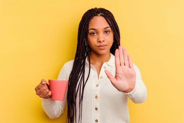 Junge afroamerikanerfrau, die einen becher lokalisiert hält, der mit ausgestreckter hand steht, die stoppschild zeigt, das sie verhindert.