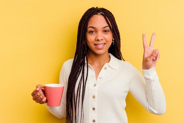 Junge afroamerikanerfrau, die einen becher lokalisiert hält, der nummer zwei mit den fingern zeigt