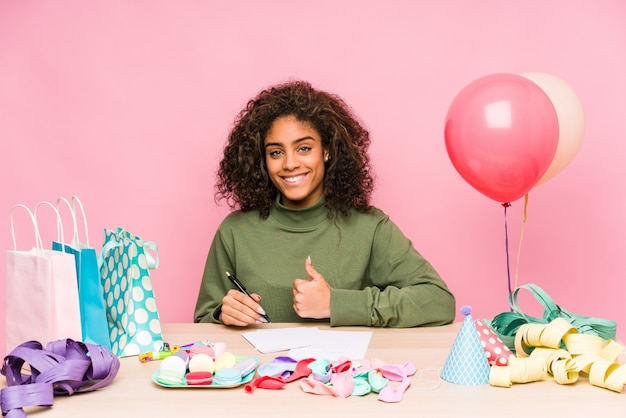 Junge afroamerikanerfrau, die einen geburtstag lächelt und oben daumen anhebt plant