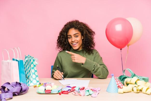 Junge afroamerikanerfrau, die einen geburtstag plant, der lächelt und beiseite zeigt und etwas an der leeren stelle zeigt.