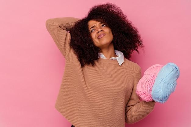 Junge afroamerikanerfrau, die einen nähfaden lokalisiert auf rosa hintergrund hält, der hinterkopf berührt, denkt und eine wahl trifft.