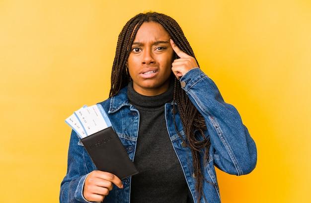 Junge afroamerikanerfrau, die einen pass hält, der eine enttäuschungsgeste mit zeigefinger zeigt.