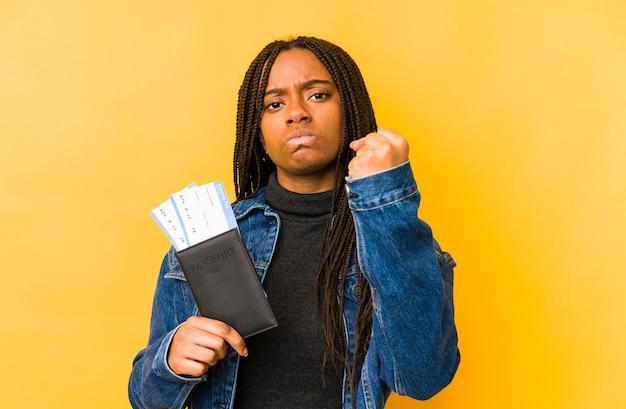 Junge afroamerikanerfrau, die einen pass lokalisiert hält, zeigt faust zur kamera, aggressiven gesichtsausdruck.