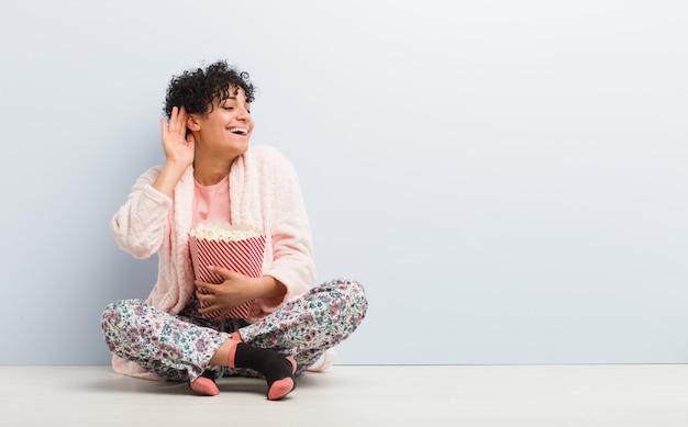 Junge afroamerikanerfrau, die einen popcorneimer versucht, einen klatsch zu hören hält.