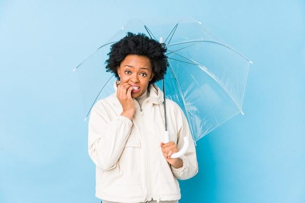 Junge afroamerikanerfrau, die einen regenschirm hält, isolierte beißende fingernägel, nervös und sehr ängstlich.