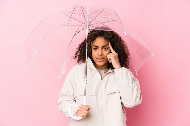 Junge afroamerikanerfrau, die einen regenschirm zeigt eine enttäuschungsgeste mit dem zeigefinger hält.