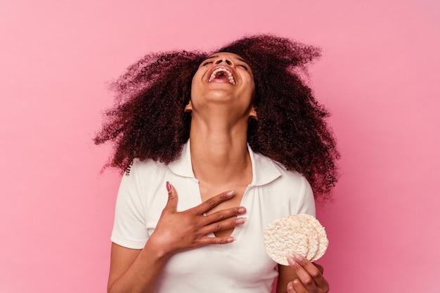 Junge afroamerikanerfrau, die einen reiskuchen isst, der auf rosa hintergrund lokalisiert wird, lacht laut und hält hand auf brust.