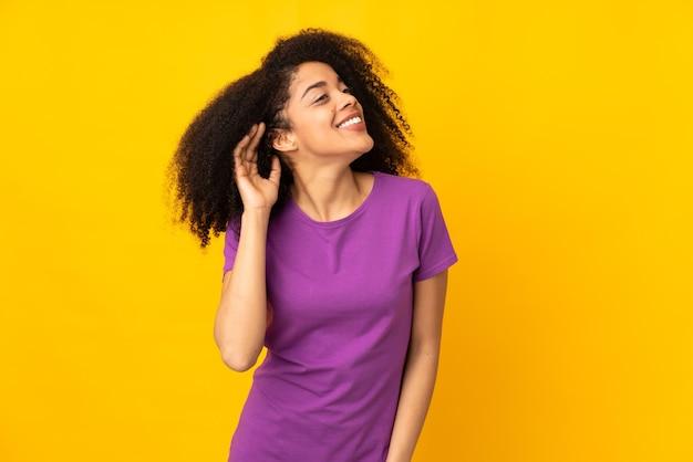 Junge afroamerikanerfrau, die etwas hört, indem man hand auf das ohr legt