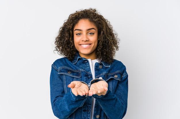 Junge afroamerikanerfrau, die etwas mit handflächen hält und kamera anbietet.