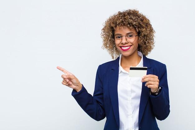 Junge afroamerikanerfrau, die fröhlich lächelt, sich glücklich fühlt und zur seite und nach oben zeigt, objekt im kopienraum mit einer kreditkarte zeigend