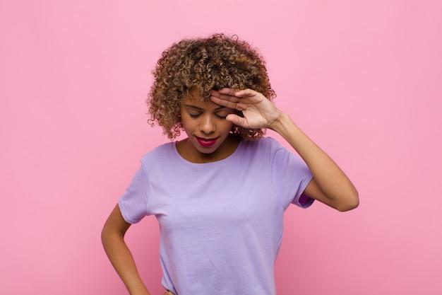 Junge afroamerikanerfrau, die gestresst, müde und frustriert schaut, schweiß von der stirn trocknet, sich hoffnungslos und erschöpft gegen rosa wand fühlt