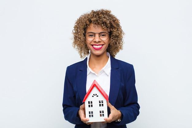 Junge afroamerikanerfrau, die glücklich mit einer hand auf hüfte und selbstbewusste, positive, stolze und freundliche haltung mit hausmodell lächelt