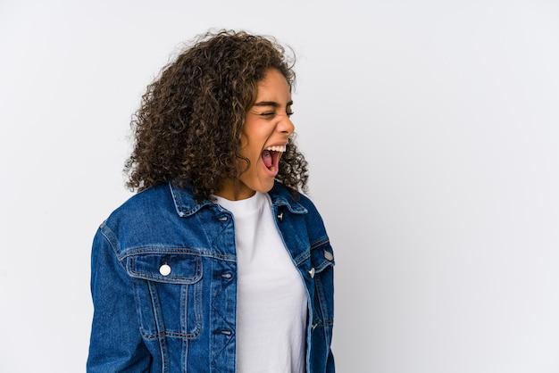 Junge afroamerikanerfrau, die in richtung zu einem kopienraum schreit