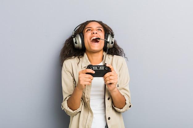 Junge afroamerikanerfrau, die kopfhörer und gamecontroller verwendet