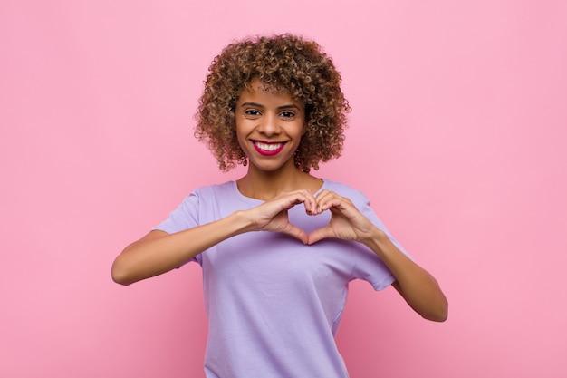 Junge afroamerikanerfrau, die lächelt und sich glücklich, niedlich, romantisch und verliebt fühlt und herzform mit beiden händen gegen rosa wand macht