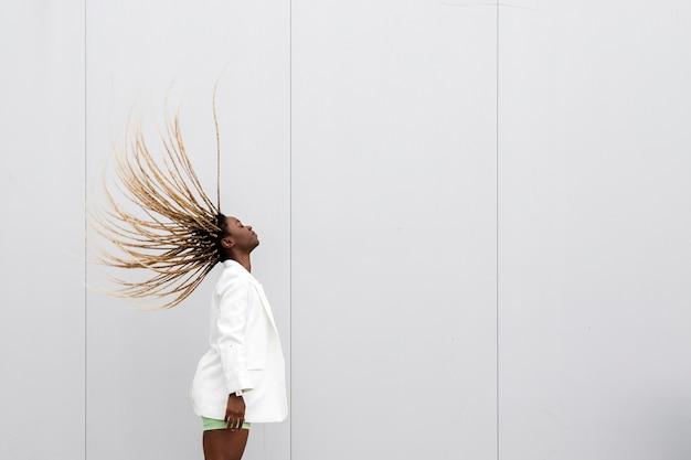Junge afroamerikanerfrau, die langes blondes geflochtenes haar zurück wirft. platz kopieren.