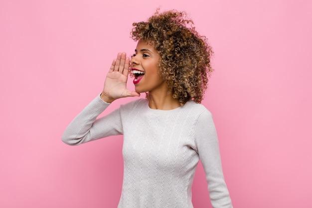 Junge afroamerikanerfrau, die laut und wütend schreit, um raum auf der seite zu kopieren, mit hand neben mund gegen rosa wand